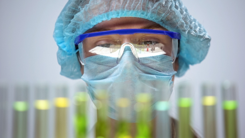 Female researcher in protective mask analyzing test tubes reaction, experiment